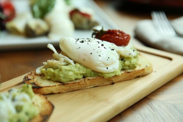 Pochiertes ei auf toast mit avocado. ein appetitliches frühstück wird auf einem holzbrett serviert.
