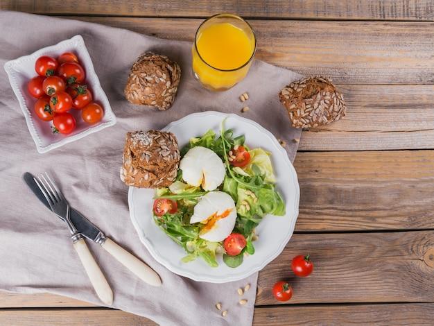 Pochiertes ei mit grünem salat, tomaten, vollkornbrot und orangensaft auf holz.