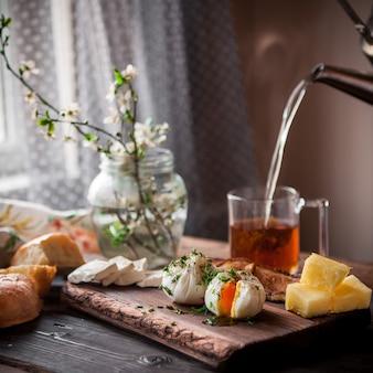 Pochiertes ei von der seite mit tasse tee und käse und blumen im glas im bordkochgeschirr