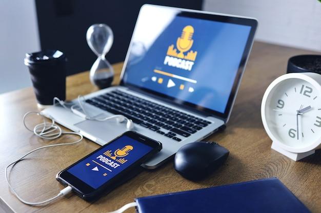 Podcast-konzept auf laptop- und smartphone-bildschirm über holztisch.