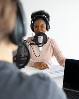 Podcaster afroamerikanische und europäische frau mit kopfhörern und mikrofon