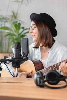 Podcaster erstellt zufriedene musikerin mit gitarrenaufzeichnungen podcast mit mikrofon und