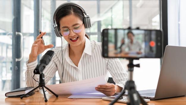 Podcasting-podcasting der asiatischen frauen und aufzeichnung der online-talkshow im studio unter verwendung von kopfhörern, professionellem mikrofon und computer-laptop auf tisch, die kamera für radio-podcast betrachten.