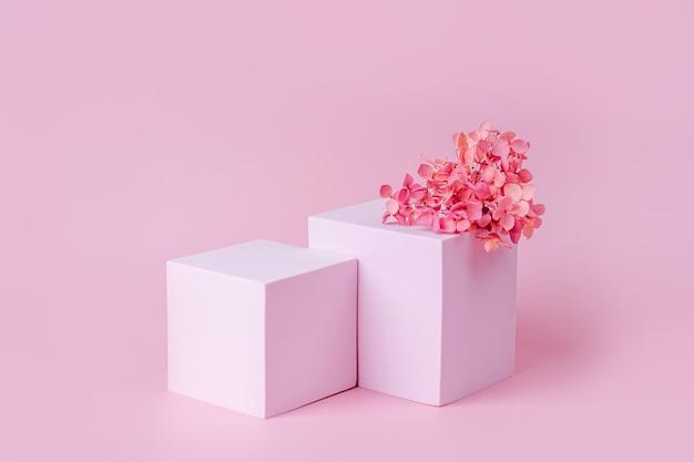 Podium mit geometrischen formen für die produktpräsentation. monochrome plattform mit blumen auf rosa hintergrund