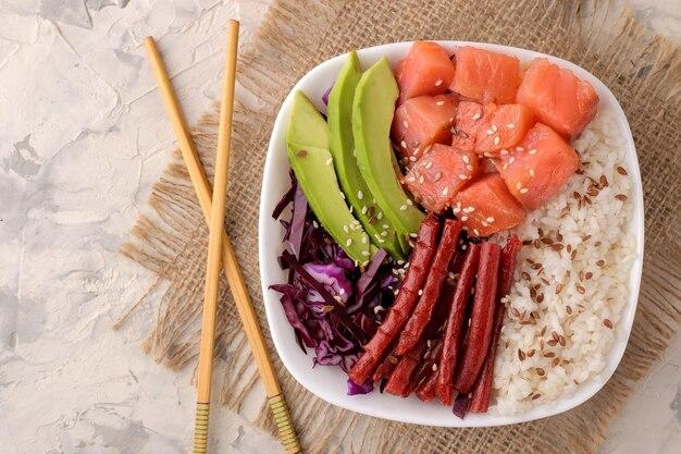 Poke bowl hawaiianisches essen. ein teller mit reis, lachs, avocado, kohl und käse auf hellem hintergrund mit stäbchen. sicht von oben