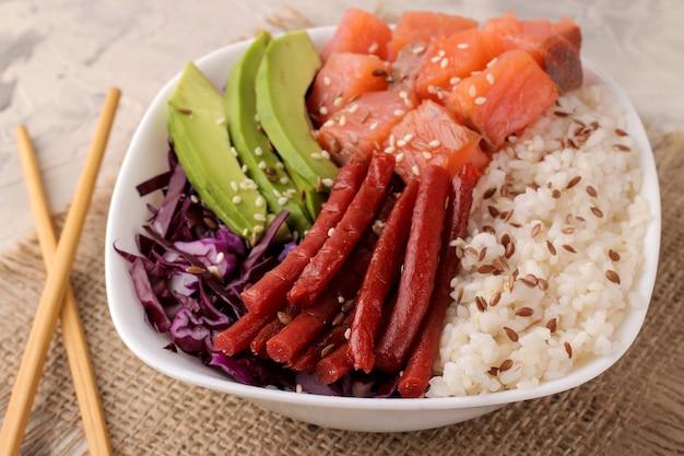 Poke bowl hawaiianisches essen. ein teller mit reis, lachs, avocado, kohl und käse auf hellem hintergrund mit stäbchen.