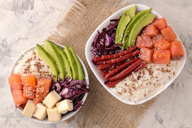 Poke bowl hawaiianisches essen. ein teller mit reis, lachs, avocado, kohl und käse auf hellem hintergrund.