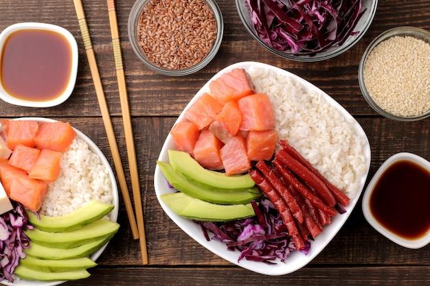 Poke bowl hawaiianisches essen. ein teller mit reis, lachs, avocado, kohl und käse, dazu sesam und sojasauce. auf einem braunen holztisch. ansicht von oben
