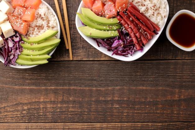 Poke bowl hawaiianisches essen. ein teller mit reis, lachs, avocado, kohl und käse, dazu sesam und sojasauce. auf einem braunen holztisch. draufsicht mit platz für text