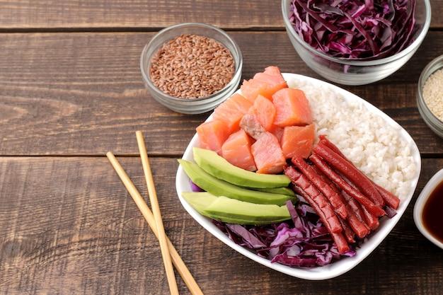Poke bowl hawaiianisches essen. ein teller mit reis, lachs, avocado, kohl und käse, dazu sesam und sojasauce. auf einem braunen holztisch.