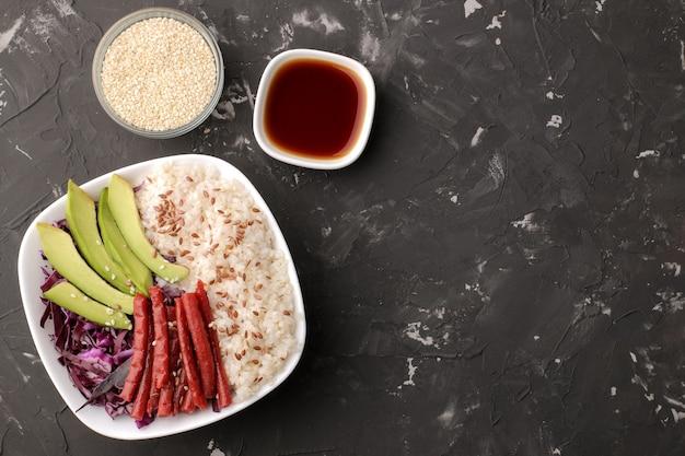 Poke bowl hawaiianisches essen. ein teller mit reis, lachs, avocado, kohl und käse. in der nähe von stinktier und sojasauce auf schwarzem hintergrund. draufsicht mit platz für text