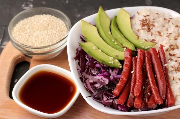 Poke bowl hawaiianisches essen. ein teller mit reis, lachs, avocado, kohl und käse. in der nähe von stinktier und sojasauce auf schwarzem hintergrund. nahaufnahme