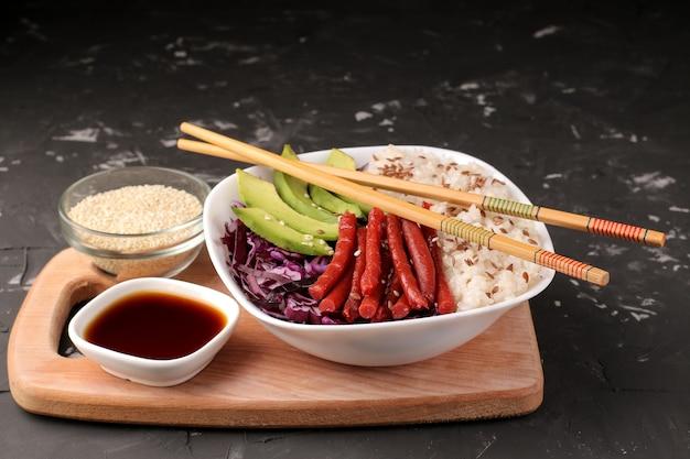 Poke bowl hawaiianisches essen. ein teller mit reis, lachs, avocado, kohl und käse. in der nähe von stinktier und sojasauce auf schwarzem hintergrund.