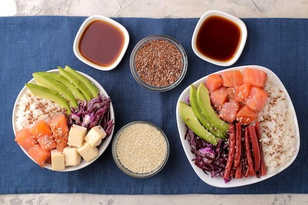 Poke bowl hawaiianisches essen. ein teller mit reis, lachs, avocado, kohl und käse neben einem stinktier und sojasauce auf einer blauen serviette auf hellem hintergrund. ansicht von oben
