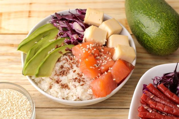 Poke bowl hawaiianisches essen. ein teller mit reis, lachs, avocado, kohl und käse. neben sesam auf einem naturholztisch