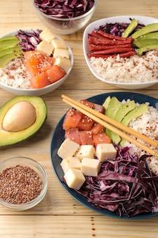 Poke bowl hawaiianisches essen. ein teller mit reis, lachs, avocado, kohl und käse. neben sesam und frischer avocado auf einem naturholztisch