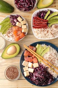 Poke bowl hawaiianisches essen. ein teller mit reis, lachs, avocado, kohl und käse. neben sesam und frischer avocado auf einer natürlichen holztischplatte.