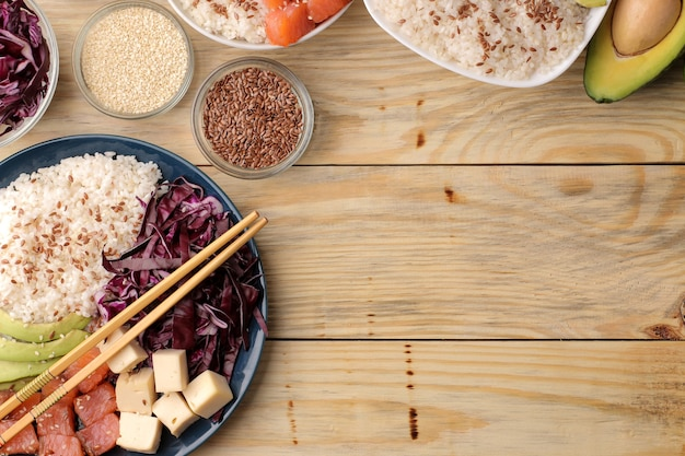 Poke bowl hawaiianisches essen. ein teller mit reis, lachs, avocado, kohl und käse. neben sesamsamen auf einer natürlichen holztisch-draufsicht. mit platz für text
