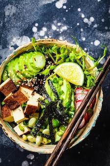 Poke bowl mit avocado, schwarzem reis, geräuchertem tofu, gemüse, sprossen