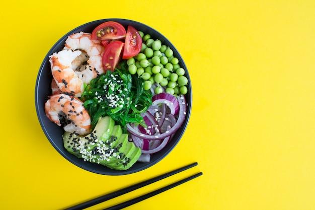 Poke bowl mit roten garnelen und gemüse in der dunklen schüssel auf der gelben oberfläche.