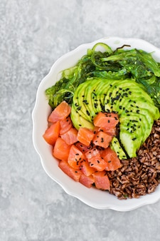 Poke bowl. zutaten: lachs, avocado, brauner reis, algen.