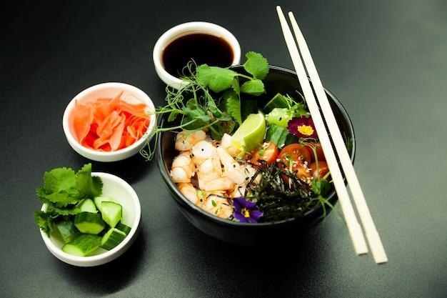 Poke-salat mit garnelen in einer schüssel zutaten garnelen blanchierter spinat kirschtomaten reis gurke soja-ingwer-sauce scharfe sauce nori sesam limette koriander asiatisches meeresfrüchte-salat-konzept