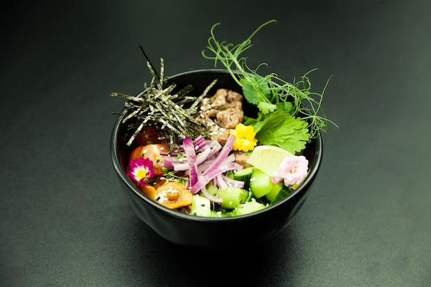 Poke salat mit rindfleisch in einer schüssel zutaten beef nameko champignons kirschtomaten reis gurke rot
