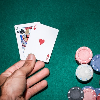 Poker-spieler hält jack spaten und herz ass spielkarte am pokertisch