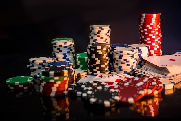 Pokerchips und spielkarte auf schwarzem tisch.