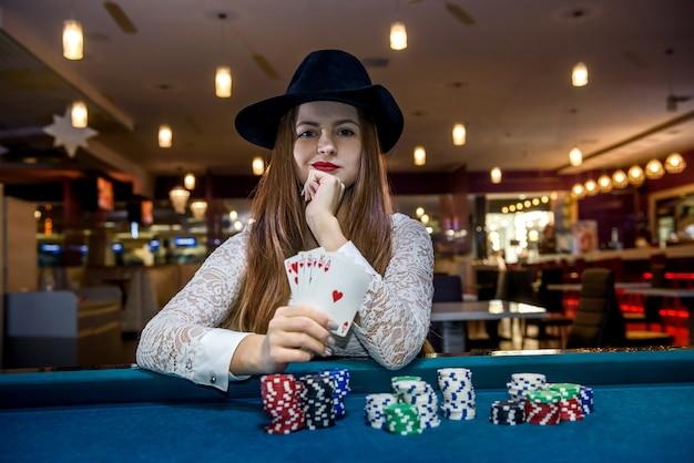 Pokerchips und weibliche hände, die spielkarten halten