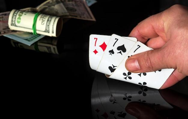 Pokerkarten mit drei einzigartigen set-kombinationen. nahaufnahme einer spielerhand hält spielkarten im kasino
