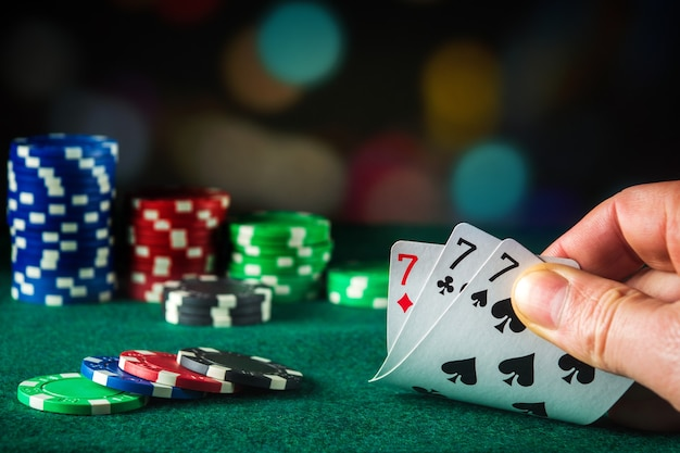 Pokerkarten mit drilling oder set-kombination. nahaufnahme der spielerhand nimmt spielkarten im pokerclub