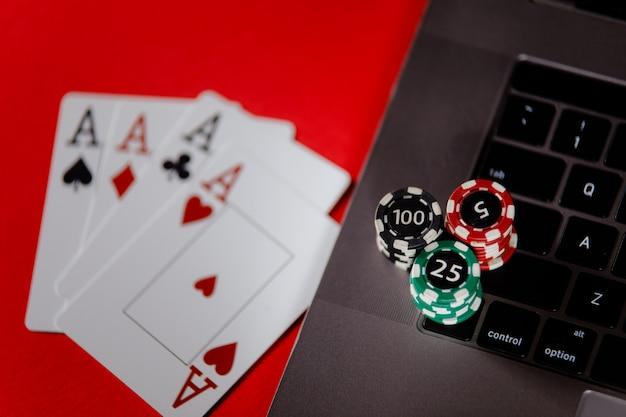 Pokerkarten, stapel von pokerchips und laptop auf einer roten hintergrundnahaufnahme.
