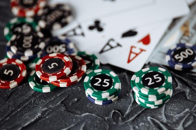 Pokerkarten und stapel von pokerchips auf grauem hintergrund. poker online-konzept.