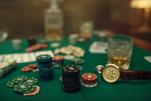 Pokerkonzept, geldwette, karten und chips am spieltisch, whisky und zigarre im casino.
