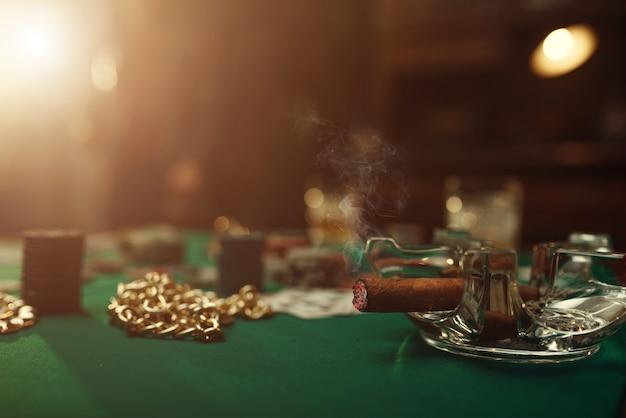 Pokerkonzept, karten und chips auf spieltischnahaufnahme, whisky und zigarre im casino