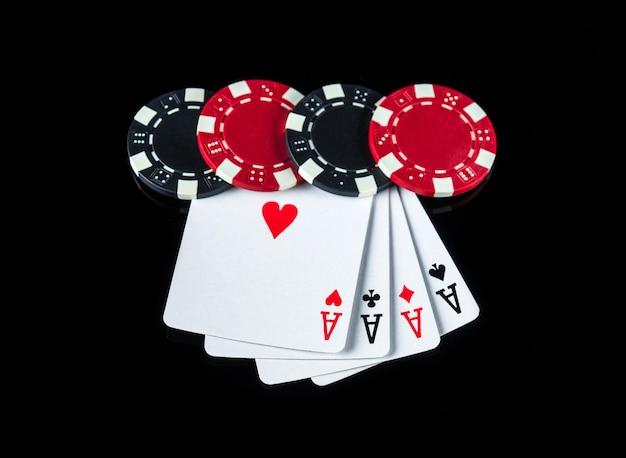 Pokerspiel mit einer vierling- oder quads-kombination. chips und karten auf dem schwarzen tisch im pokerclub
