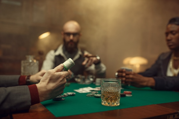 Pokerspieler hält geldrolle, casino. sucht, risiko, spielhaus
