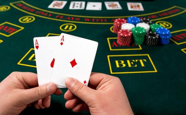 Pokerspieler hält karten. ansicht aus der ersten person. zwei asse, eine gewinnkombination. männliche hände