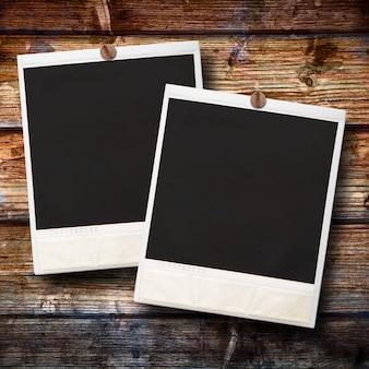 Polaroid zwei, das am hölzernen hintergrund hängt