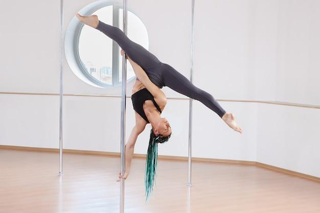 Pole-dance-training im fitnessstudio fitness-studio-übungsleistung einer anmutigen frau