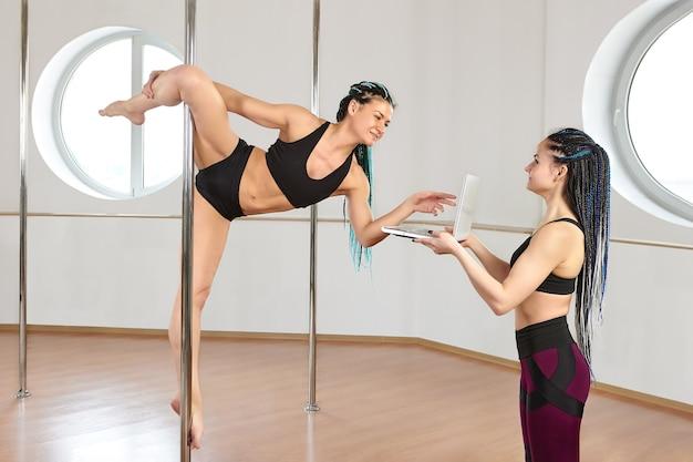 Pole dancer trainiert durch das studium von video-tutorials im fitnessstudio
