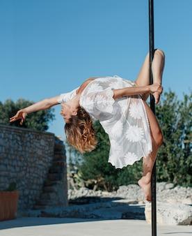 Pole tänzer posiert auf einer tragbaren plattform gegen den garten