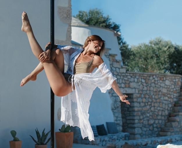 Pole tänzer posiert auf einer tragbaren plattform gegen die villa wand