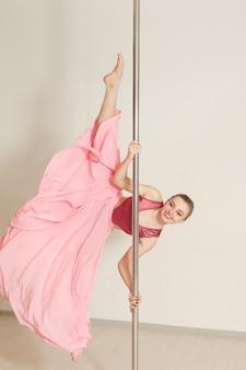 Poledance frau, die im schönen rosa kleid streckt