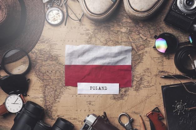 Polen-flagge zwischen dem zubehör des reisenden auf alter weinlese-karte. obenliegender schuss