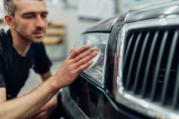 Polieren des autoscheinwerfers beim autowaschdienst