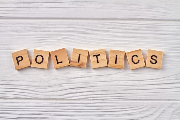 Politik und regierungskonzept. buchstaben auf holzwürfeln isoliert auf holzbrett.