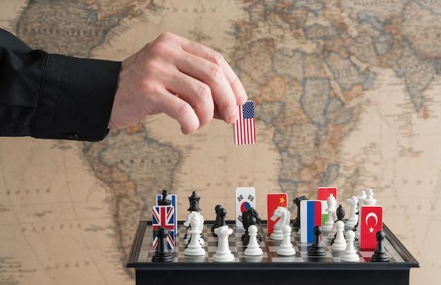 Politiker hand bewegt eine schachfigur mit einer flagge konzeptfoto eines politischen spiels