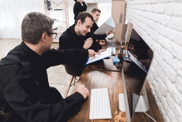 Polizeibeamte arbeiten an einem computer in der polizeistation.